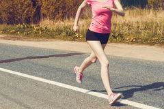 Young lady running on a rural road Royalty Free Stock Image