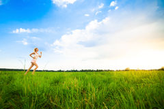 Young lady running on a rural road during sunset Royalty Free Stock Image