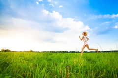 Young lady running on a rural road during sunset Stock Photo
