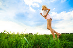 Young lady running on a rural road during sunset Stock Image