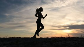 Young lady running on seashore at sunset stock video footage