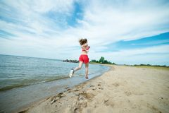 Young lady running at the sunny summer sand beach Royalty Free Stock Images