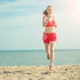 Young lady running at the sunny summer sand beach Stock Photos
