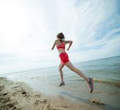 Young lady running at the sunny summer sand beach Royalty Free Stock Photos