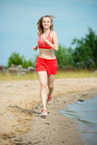 Young lady running at the sunny summer sand beach Royalty Free Stock Image