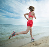 Young lady running at the sunny summer sand beach Royalty Free Stock Photo