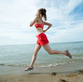 Young lady running at the sunny summer sand beach Stock Image
