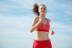Young lady running at the sunny summer sand beach Royalty Free Stock Photography