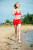 Young lady running at the sunny summer sand beach. Workout.  Jog Stock Image