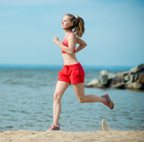 Young lady running at the sunny summer sand beach. Workout.  Jog Royalty Free Stock Images