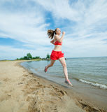 Young lady running at the sunny summer sand beach. Workout.  Jog Stock Photos