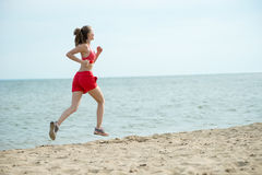 Young lady running at the sunny summer sand beach. Workout.  Jog Royalty Free Stock Photography