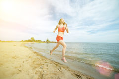 Young lady running at the sunny summer sand beach. Workout.  Jog Royalty Free Stock Photo