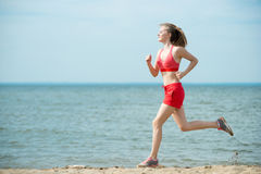 Young lady running at the sunny summer sand beach. Workout.  Jog. Young lady running. Woman runner running at the sunny summer sand beach. Workout near ocean sea Royalty Free Stock Photos