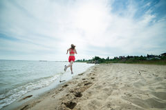 Young lady running at the sunny summer sand beach. Workout.  Jog Stock Photography