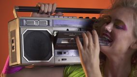 Lady from the 80s puts a cassette into the boombox and enjoys the music. Young lady from the 80s, in colorful clothes, puts a cassette into the vintage boombox stock footage