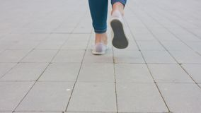 Young Lady`s Feet Walking on the Cobblestone. Close-up shot Royalty Free Stock Photos