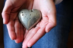 Young lady's hands holding a heart. Young woman's cupped hands holding a stone heart,as a symbol of her own, in the center of them royalty free stock image