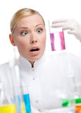 Young lady scientist wonders at the beaker Royalty Free Stock Photos