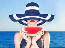 Young lady at sea with watermelon. Young stylish lady in a hat at sea with watermelon Royalty Free Stock Image