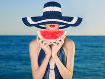 Young lady at sea with watermelon. Young stylish lady in a hat at sea with watermelon Royalty Free Stock Photo