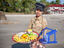 Young lady sells fresh fruit along the beach Royalty Free Stock Photos