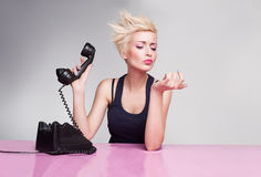 Ignoring phone. Young lady with short blond hair holding handset and not listening the phone Stock Images