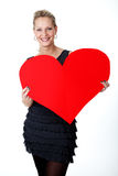Young lady shows a big, red heart Royalty Free Stock Image