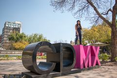 Young lady siiting on the CDMX sculpture in la Condesa. Young lady sitting on the CDMX sculpture in la Condesa royalty free stock photo