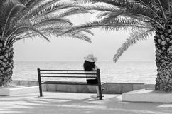 Young lady sitting on bench looking at sea on sunny summer day Stock Images