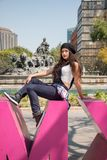 Young lady sitting  on the CDMX sculpture in la Condesa. Young lady sitting on the CDMX sculpture in la Condesa royalty free stock photos