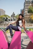 Young lady sitting  on the CDMX sculpture in la Condesa. Young lady sitting on the CDMX sculpture in la Condesa royalty free stock photo