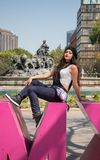 Young lady sitting  on the CDMX sculpture in la Condesa. Young lady sitting on the CDMX sculpture in la Condesa royalty free stock image