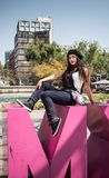 Young lady sitting  on the CDMX sculpture in la Condesa. Young lady sitting on the CDMX sculpture in la Condesa royalty free stock photography