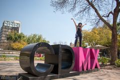 Young lady standing on the CDMX sculpture in la Condesa. Young lady sitting on the CDMX sculpture in la Condesa royalty free stock image