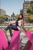 Young lady sitting  on the CDMX sculpture in la Condesa. Young lady sitting on the CDMX sculpture in la Condesa stock photo