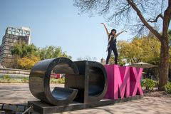 Young lady standing on the CDMX sculpture in la Condesa. Young lady sitting on the CDMX sculpture in la Condesa stock photos