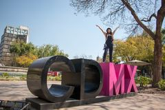 Young lady standing on the CDMX sculpture in la Condesa. Young lady sitting on the CDMX sculpture in la Condesa stock photo