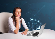 Young lady sitting at desk and typing on laptop with social netw Royalty Free Stock Photo