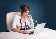 Young lady sitting at desk and typing on laptop with social netw Stock Photos