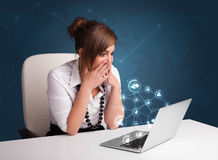 Young lady sitting at desk and typing on laptop with social netw Royalty Free Stock Image