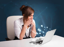 Young lady sitting at dest and typing on laptop with message ico Stock Photography