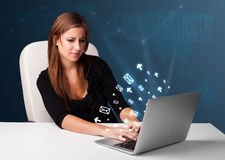 Young lady sitting at dest and typing on laptop with message ico Royalty Free Stock Images
