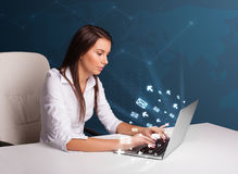 Young lady sitting at dest and typing on laptop with message ico Royalty Free Stock Image