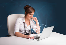Young lady sitting at dest and typing on laptop with message ico Stock Photo