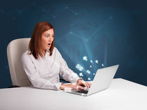 Young lady sitting at dest and typing on laptop with message ico Stock Photos