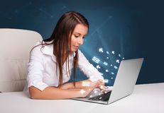 Young lady sitting at dest and typing on laptop with message ico Stock Images