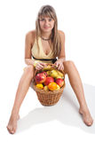 Young lady sitting with fruit basket Royalty Free Stock Images