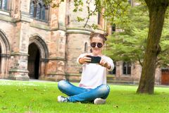 Young lady sitting on the grass in Glasgow University garden. Young lady sitting on the grass and taking photography in Glasgow University garden. Summertime Royalty Free Stock Photography