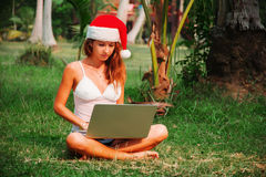 Young lady is sitting on the grass with a laptop in a christmas hat. In the jungle Stock Photos